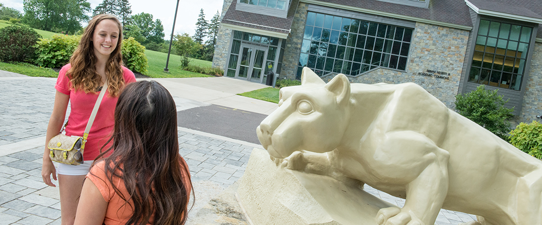 Two students talk in front of the Nittany Lion statue on the Penn State Wilkes Barre campus.